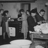 Gerson Frydman peeling potatoes, black cap looking toward right. (far left) Vera Stern. Windermere 1945.